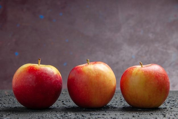 Vista lateral de perto frutas três maçãs amarelo-avermelhadas em uma mesa de madeira cinza sobre um fundo roxo
