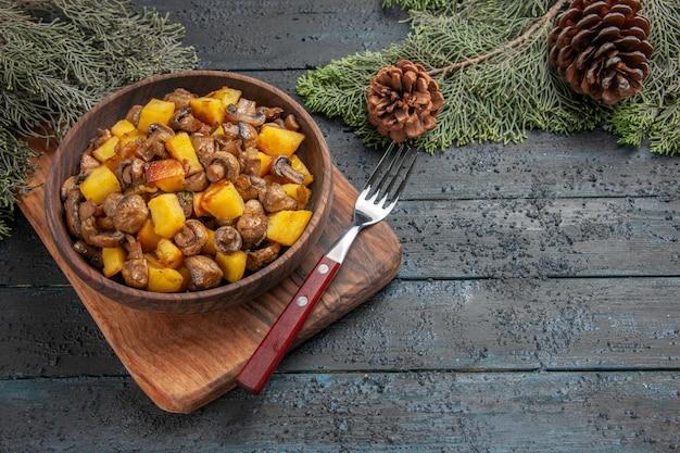 Vista lateral de perto prato e tábua de cortar tigela marrom de cogumelos e batatas ao lado do garfo e tábua de cortar sob os ramos de abeto com cones
