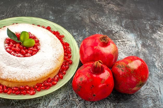 Vista lateral de perto um bolo apetitoso um bolo apetitoso com frutas cítricas e três romãs