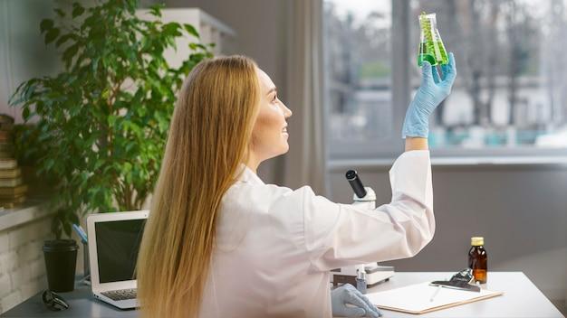 Vista lateral de pesquisadora com luvas no laboratório segurando tubo de ensaio