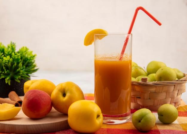 Vista lateral de pêssegos amarelos doces em uma placa de cozinha de madeira com pêssego rosa-laranja com suco de pêssego com ameixas de cereja verdes em um balde em uma toalha de mesa quadriculada em um fundo branco