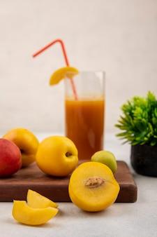 Vista lateral de pêssegos amarelos doces frescos em uma placa de cozinha de madeira com suco de pêssego em um fundo branco