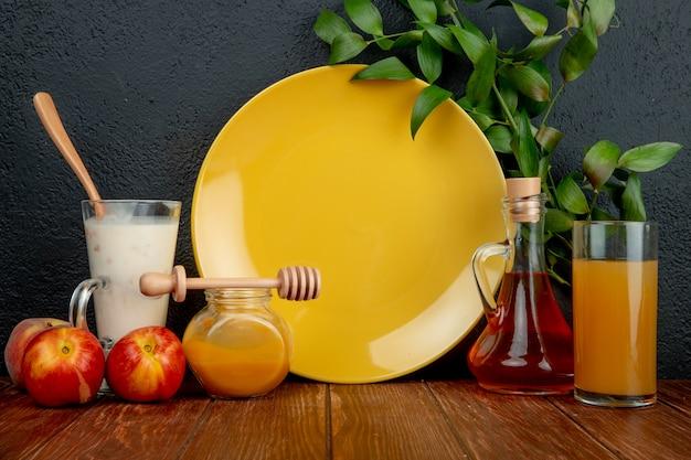 Vista lateral de pêssegos com copo de iogurte geléia de ameixa xarope de pêssego e suco com prato vazio na superfície de madeira