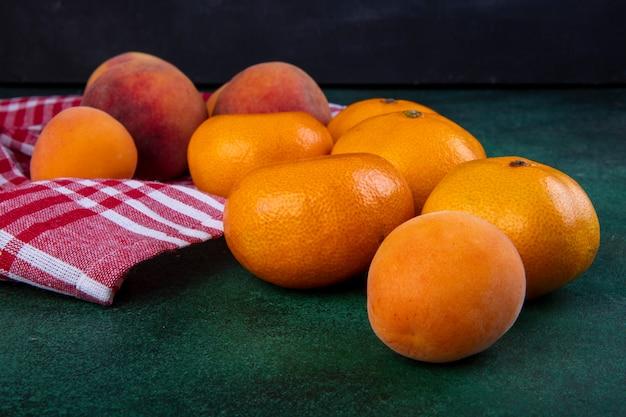 Vista lateral de pêssegos com tangerinas e damascos na toalha de cozinha