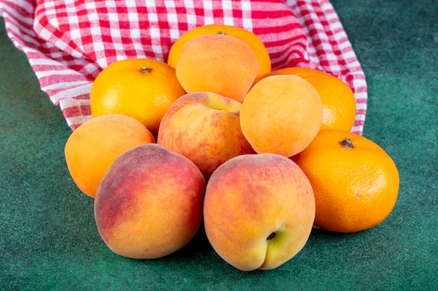 Vista lateral de pêssegos doces maduros frescos e tangerinas em tecido xadrez no escuro