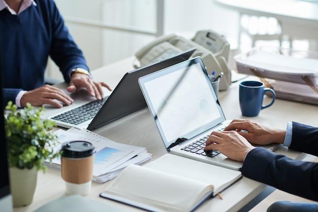 Vista lateral de pessoas de negócios irreconhecíveis cortadas, trabalhando na mesa comum