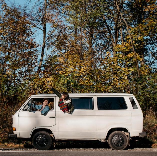Vista lateral de pessoas fazendo uma excursão em uma van branca