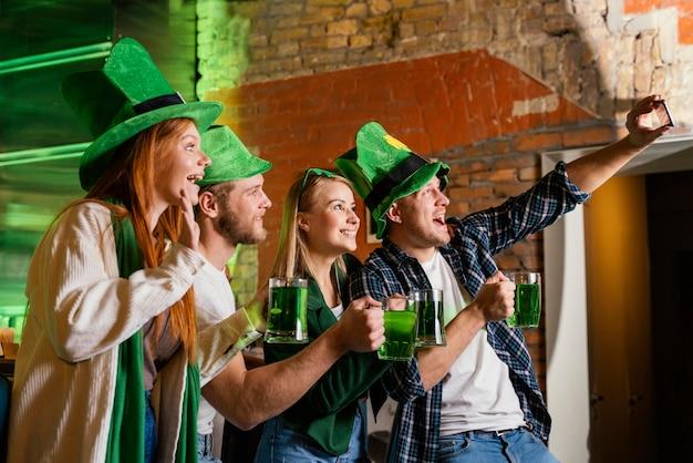 Vista lateral de pessoas felizes celebrando st. patrick's day e tirando selfie