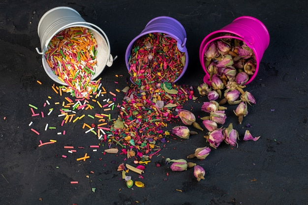 Vista lateral de pétalas de flores secas de chá de rosa e granulado colorido espalhados de pequenos baldes no preto