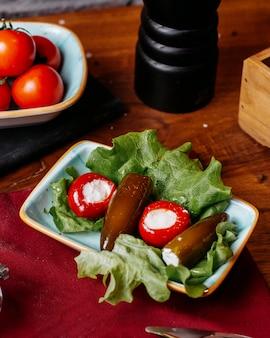 Vista lateral de picles de tomate e berinjela cheia de queijo branco em uma mesa de madeira