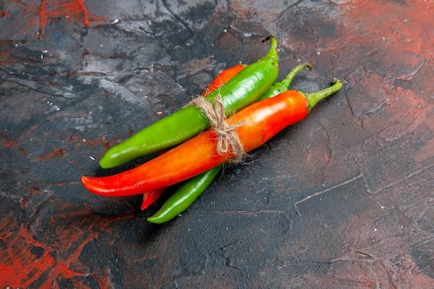 Vista lateral de pimenta caiena em diferentes cores e tamanhos amarrados uns nos outros com corda na mesa de cores misturadas
