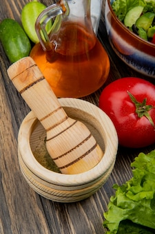 Vista lateral de pimenta preta no triturador de alho com salada de vegetais e sal de pepino tomate tomate derretido na superfície de madeira