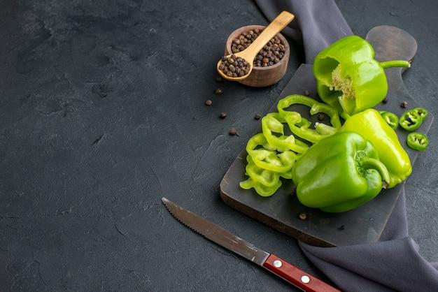 Vista lateral de pimentões verdes cortados inteiros em uma tábua de madeira em uma superfície de cor escura