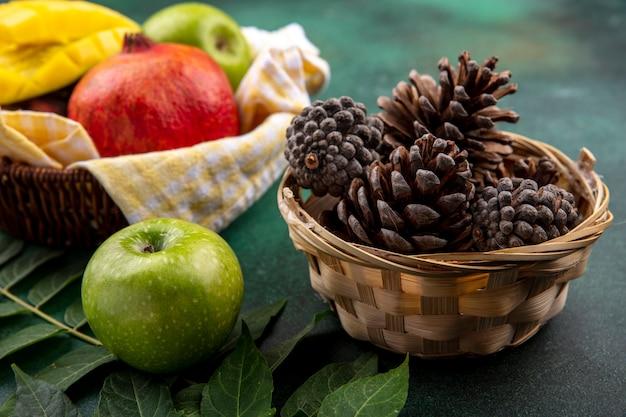 Vista lateral de pinhas secas em um balde com frutas frescas, como manga romã maçã no busket verificado amarelo com folhas na superfície preta