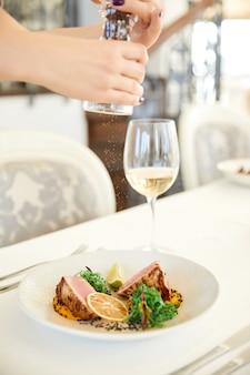 Vista lateral de polvilhar com especiarias um prato de atum com copo de vinho branco no restaurante
