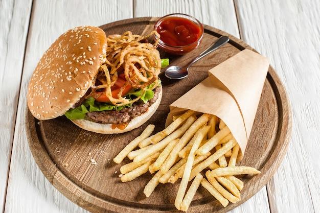 Vista lateral de prato de bufê com hambúrguer americano tradicional com batata frita