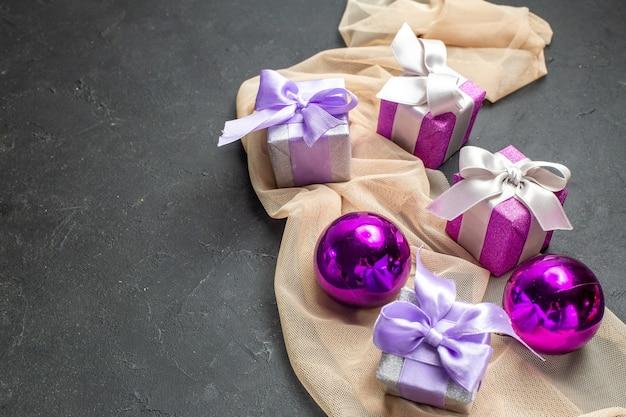 Vista lateral de presentes coloridos e acessórios de decoração para o natal em fundo preto