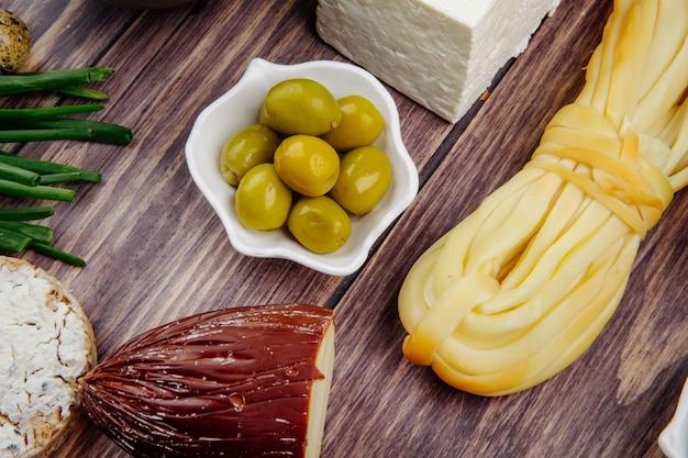 Vista lateral de queijo defumado e corda com azeitonas em conserva em madeira rústica