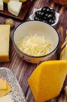 Vista lateral de queijo holandês ralado em uma tigela e azeitonas em conserva pretas na madeira rústica