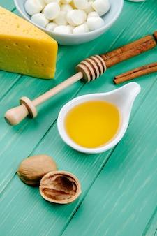 Vista lateral de queijo mussarela com um pedaço de queijo holandês com nozes mel e paus de canela na madeira verde