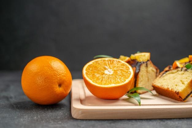 Vista lateral de rodelas de limão fresco e fatias de bolo recém-assado na mesa escura
