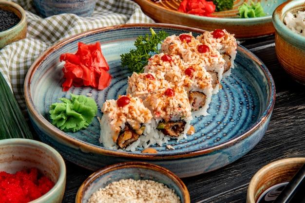 Vista lateral de rolos de sushi com arroz camarão tempura abacate e queijo dentro de um prato com gengibre e wasabi
