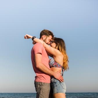 Vista lateral, de, romanticos, par jovem, ficar, contra, céu azul, em, praia