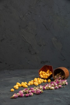 Vista lateral de rosas secas espalhadas da cesta com pipoca doce polvilhada