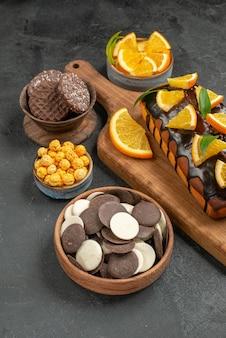 Vista lateral de saborosos bolos cortados em laranjas com biscoitos na tábua de cortar na mesa escura
