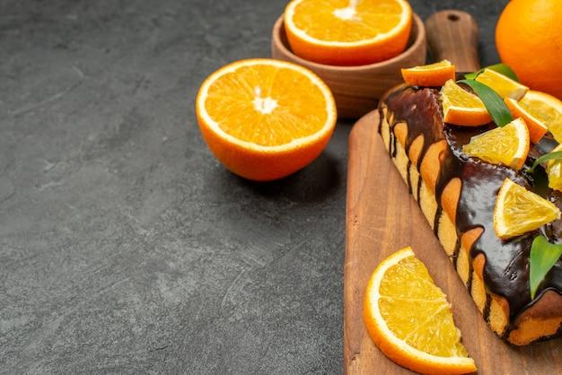 Vista lateral de saborosos bolos inteiros e laranjas cortadas na tábua de cortar na mesa preta