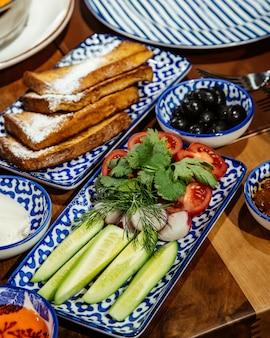 Vista lateral de salada fresca com pepinos, ervas e tomates, servidos com torradas e azeitonas pretas