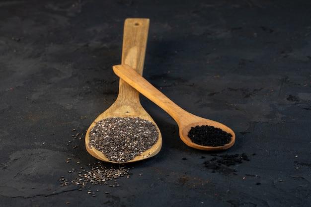 Vista lateral de sementes de cominho preto em colheres de pau no preto