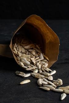 Vista lateral de sementes de girassol brancas espalhadas de um saco de pimenta no preto