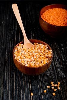 Vista lateral de sementes de milho secas em uma tigela com colher de pau na mesa rústica preta