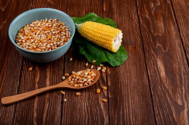 Vista lateral de sementes de milho secas na tigela e colher de pau com milho cozido e espinafre na mesa de madeira com espaço de cópia