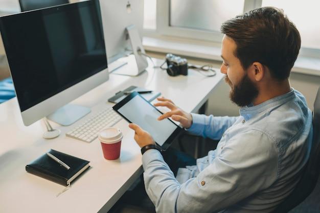 Vista lateral de sentar-se no local de trabalho com computador, câmera e copo de papel masculino com barba por fazer a tela de rolagem do tablet nas mãos