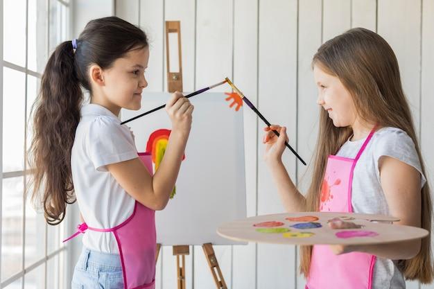Vista lateral, de, sorrindo, duas meninas, tocar, seu, escovas pintura, enquanto, quadro, ligado, lona