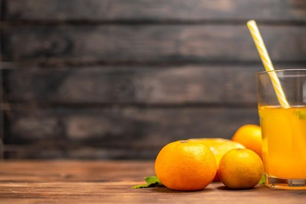 Vista lateral de suco de laranja fresco em um copo servido com tubo de hortelã e laranjas inteiras cortadas em uma mesa de madeira
