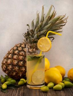 Vista lateral de suco de limão rico em vitaminas em um copo com limões de abacaxi e kinkans isolados em uma mesa de madeira sobre uma superfície branca