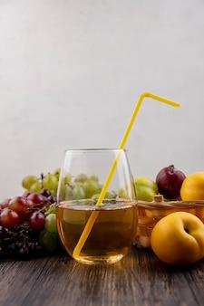 Vista lateral de suco de uva branca em vidro com frutas como nectacotes plumas em uma cesta com uvas em superfície de madeira e fundo branco