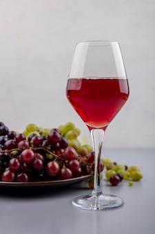 Vista lateral de suco de uva preta em um copo de vinho e prato de uvas com bagas de uva na superfície cinza e fundo branco