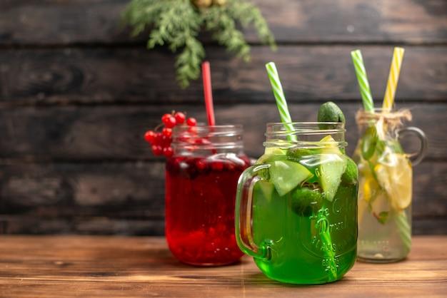Vista lateral de sucos naturais orgânicos em garrafas servidas com tubos e frutas no lado esquerdo em um fundo de madeira marrom