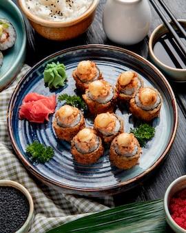 Vista lateral de sushi assado rola com camarão gengibre e wasabi em um prato servido com molho de soja na madeira