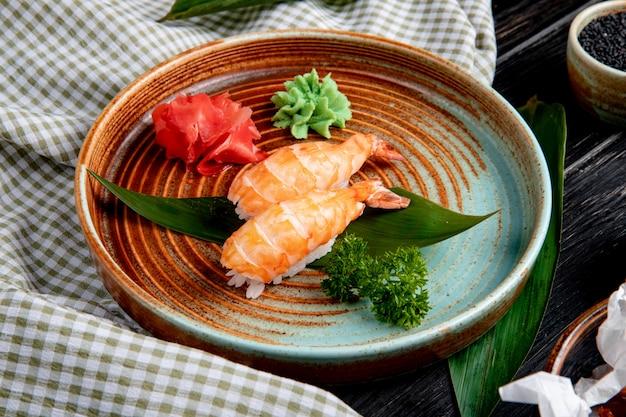 Vista lateral de sushi nigiri de camarão na folha de bambu, servido com fatias de gengibre em conserva e wasabi em um prato