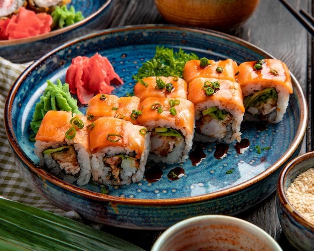 Vista lateral de sushi rolls com salmão enguia abacate e cream cheese em um prato com gengibre e wasabi