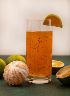 Vista lateral de tangerinas frescas e saudáveis com suco de frutas frescas em um copo em uma parede branca
