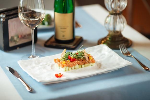 Vista lateral de tártaro de salmão espanhol em travesseiro de abacate em um prato branco