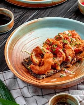 Vista lateral de tempura de camarão frito com cebolinha picada e molho num prato de madeira