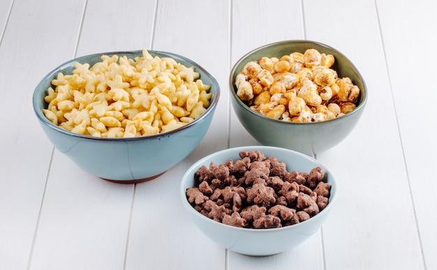 Vista lateral de tigelas de vários cereais e pipoca de caramelo doce em fundo branco de madeira