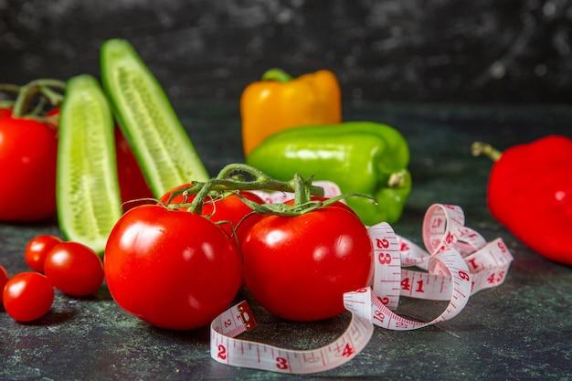 Vista lateral de tomate fresco, pimentão e medidor em superfície de cores escuras com espaço livre